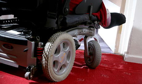 image of wheelchair user going through a door - lower portion of wheelchair only is visible