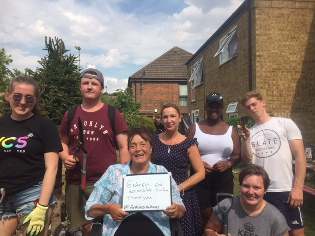 A group of tenants including Ginny Haymond pose in a garden for our #ForAccessiblehomes campaign