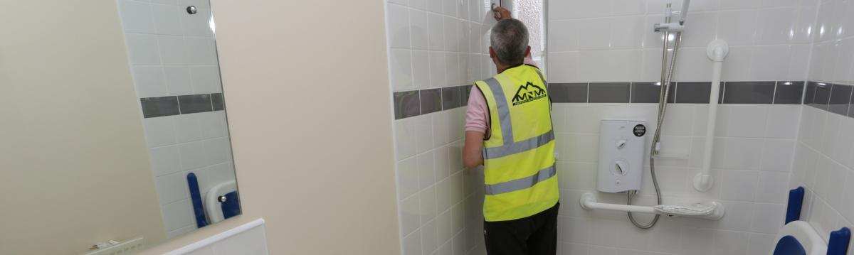 MNM property services man completing bathroom repairs